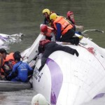 Rescuers pull a passenger out of the TransAsia Airways plane which crash landed in a river in New Taipei City